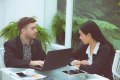 运作在现代办公室的年轻事务夫妇 库存照片