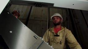 运作在电梯的建造者 工作者安装电梯设备 阿纳帕,克拉斯诺达尔地区2018年6月28日 影视素材