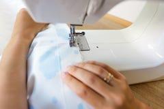 运作在缝纫机的裁缝的图象 免版税库存图片