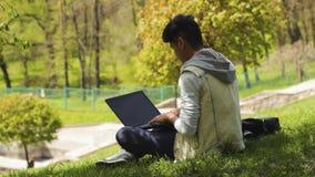 运作在膝上型计算机的公园的人程序员 股票视频