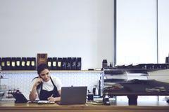 运作在自助食堂的有吸引力的女性barista画象  免版税库存图片