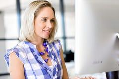 运作在计算机的女实业家画象在办公室 免版税库存图片