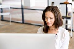 运作在计算机的女实业家画象在办公室 图库摄影