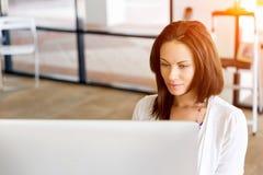 运作在计算机的女实业家画象在办公室 免版税库存照片