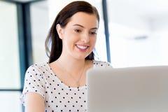 运作在计算机的女实业家画象在办公室 库存照片