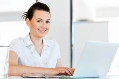 运作在计算机的女实业家画象在办公室 库存图片