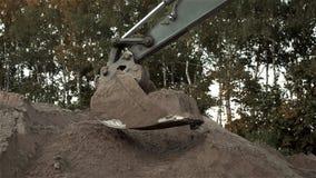 运作在道路工程期间的挖掘机开掘的沙子和尘土,地球搬家工人开掘的机器的桶射击的关闭  股票录像