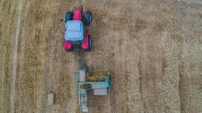 运作在麦田的拖拉机空中寄生虫视图创造秸杆大包,干草堆 免版税库存照片