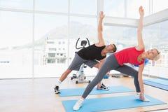 运作在锻炼席子的愉快的适合夫妇 免版税图库摄影