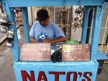运作在他的沿一条街道的小摊位的一个不加考虑表赞同的人制造商在安蒂波洛市,菲律宾 库存图片