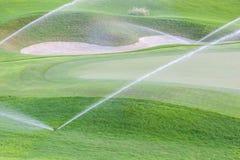 运作在绿色高尔夫球场的喷水隆头供水系统 库存图片