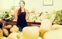 运作妇女的画象显示新鲜的绿色莴苣在果子 免版税库存图片