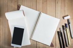 运作的对象顶视图:灰色铅笔和许多在木桌和智能手机上的黑笔在白色笔记本 免版税库存图片