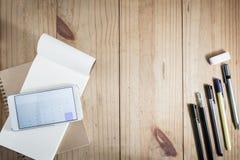 运作的对象顶视图:灰色铅笔和许多在木桌和智能手机开放计算器app的黑笔在白色笔记本 免版税库存图片