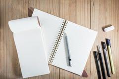运作的对象顶视图:灰色铅笔和许多黑笔在木桌上的白色笔记本附近 免版税库存照片