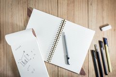 运作的对象顶视图:灰色铅笔和许多黑笔在木桌上的白色笔记本附近 免版税图库摄影