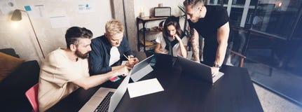 运作的片刻 小组聪明的便衣的年轻工友人民谈论事务,当工作在创造性时 免版税图库摄影