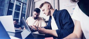 运作的片刻 小组聪明的便衣的年轻工友人民谈论事务,当工作在创造性时 免版税库存图片