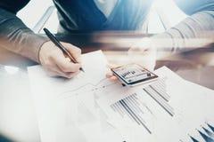 运作的过程 工作在与新的企业项目的桌上的帐户经理 握现代智能手机手 图库摄影