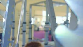 运作的防护手套的年轻可爱的妇女艰苦做在健身房的被衡量的蹲坐 股票录像