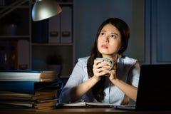 运作超时夜间的亚洲女商人饮料咖啡 免版税图库摄影
