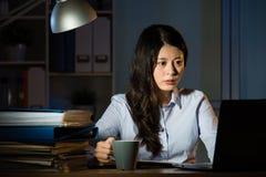 运作超时夜间的亚洲女商人饮料咖啡 免版税库存图片