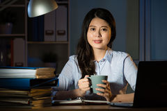 运作超时夜间的亚洲女商人饮料咖啡 库存照片