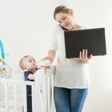 运作从家的女实业家画象与她的9个月ol 免版税库存照片