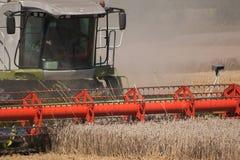 运作绿色的红色收获在麦田的组合 免版税库存照片