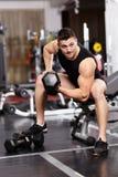 运动人与重的哑铃一起使用在健身房 免版税库存照片