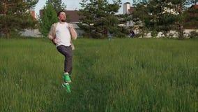 运动人在城市的公园区域做一种活跃锻炼,他跳 影视素材