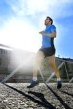 年轻运动人实践的跑在健身体育训练和健康生活方式概念的都市背景背后照明 免版税库存照片