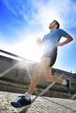 年轻运动人实践的跑在健身体育训练和健康生活方式概念的都市背景背后照明 免版税库存图片