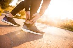 运动人赛跑者感人的脚在痛苦中由于被扭伤的脚腕 免版税库存照片