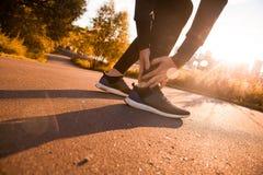 运动人赛跑者感人的脚在痛苦中由于被扭伤的脚腕 库存图片