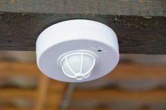 运动传感器和烟的特写镜头在屋顶下 免版税库存图片