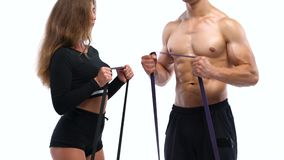 运动做二头肌的男人和妇女行使与在白色背景的橡皮筋在演播室 股票录像