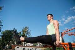运动员举行走下去培养了腿双杠,锻炼 免版税库存照片