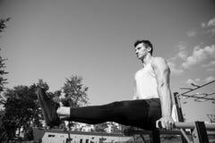运动员举行走下去培养了腿双杠,锻炼 库存图片