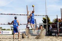 运动员人沙滩排球跳跃的钉攻击 防御 免版税库存图片