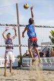 运动员人沙滩排球跳跃的钉攻击 防御 免版税库存照片