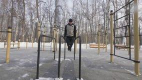 运动员人训练俯卧撑在冬季体育地面的酒吧行使 股票录像