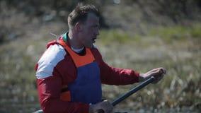 运动员划船背面图在河的独木舟的 荡桨,乘独木舟,用浆划 ?? 划皮船 人航行反对 股票录像