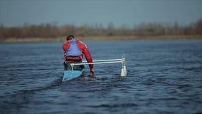 运动员划船背面图在河的独木舟的 荡桨,乘独木舟,用浆划 ?? 划皮船 股票录像