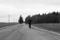 运动员在一条高速公路跑在乡下 免版税库存图片