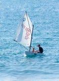 年轻运动员在一艘初级的体育帆船训练 免版税库存照片