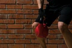 运动员在健身屋子拾起红色重量改进身体反对砖墙背景 库存照片