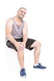 运动员在极痛苦的痛苦中的抓住膝盖 库存图片