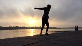 运动员在河岸愉快地转过来与里德在慢动作的日落 股票视频