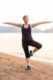 运动员在海滩的一只脚平衡 库存照片